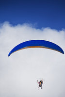 Man paragliding against background of white cloud