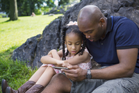 Father and daughter (6-7) sitting on grass and playing with digital tablet in park rock in background 11100027078| 写真素材・ストックフォト・画像・イラスト素材|アマナイメージズ