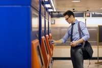 Businessman by ticket machines in subway