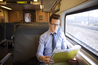 Businessman reading newspaper in train