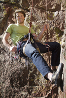 Rock climber hanging from rope