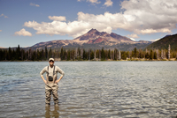 Fisherman with hands on hips standing in shallow water of lake with forest and mountain in background
