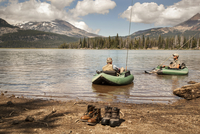 Two fishermen floating in inflatable rafts in mountain lake with their boots on shore in foreground