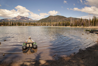 Fisherman floating in inflatable raft in lake shoals with forest and mountains in background