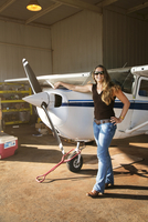Young woman standing near small airplane