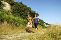 Couple running along dirt path 11100028798  写真素材・ストックフォト・画像・イラスト素材 アマナイメージズ
