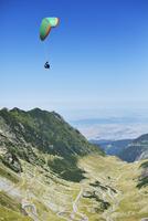 Man parachuting over valley 11100028891| 写真素材・ストックフォト・画像・イラスト素材|アマナイメージズ
