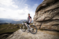 Young man standing by rock with bike, looking at camera, landscape in background
