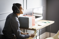 Man in office working and listening to music