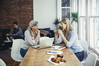 USA, New York, New York City, Two businesswomen talking at desk