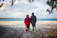 Senior couple walking on beach on sunny day