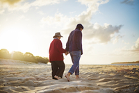 Senior couple holding hands and walking on sandy beach
