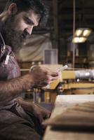 Carpenter using phone in workshop