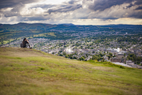 Scotland, Edinburgh, Woman sitting on grass photographing view