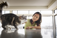 Young woman stroking cat on table