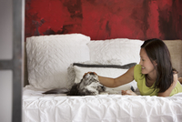 Young woman stroking cat on bed