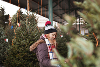 Young woman choosing Christmas tree at market