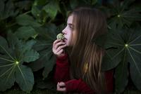 Girl smelling flower in bush