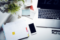 Smart phone, laptop and note pad on desk