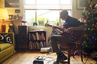 Bald man sitting on chair and playing guitar at home