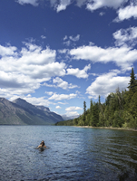 Canada, Alberta, Woman swimming in lake with mountains in background