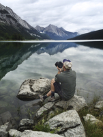 Canada, Alberta, Man sitting on rock and photographing lake with camera