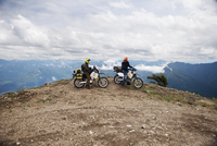 USA, Washington State, Two men driving motocrosses through Gifford Pinchot National Forest