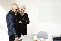 Man and senior woman looking at MacBook