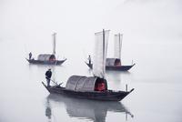 China, Zhejiang, Lishui, Men standing on boats in foggy weather