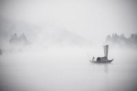 China, Zhejiang, Lishui, Yunhe, Man standing on boat in foggy weather