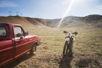 Motorcycle and pick-up truck on arid landscape against sky
