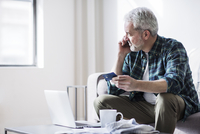 Mature man holding credit card while answering smart phone at home