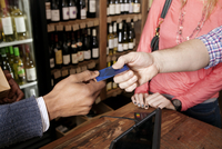 High angle view of owner taking credit card from customer at wine shop