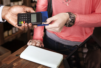 Midsection of female customer paying through credit card at wine shop