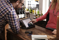 Midsection of female customer using tablet computer while paying at wine shop