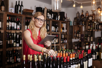 Female owner using tablet computer while working in wine shop