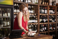 Female owner using mobile phone while working at checkout counter in wine shop 11100034076| 写真素材・ストックフォト・画像・イラスト素材|アマナイメージズ