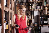Happy female owner using tablet computer while holding wine bottle in shop