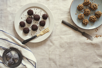 Overhead view of fresh chocolate balls in plates on table