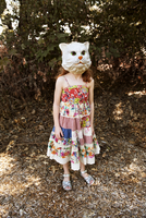 Young girl wearing cat mask outdoors