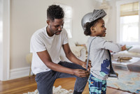 Father dressing up boy as knight in armor costume at home