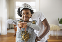 Father assisting cheerful boy in getting dressed as armor at home
