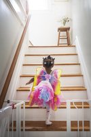 Rear view of girl dressed up in fairy costume moving up steps at home