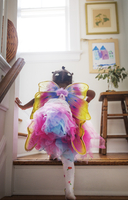 Rear view of girl in fairy costume moving up steps at home