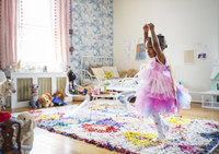 Full length of girl in fairy costume dancing at home