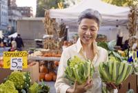 Happy mature woman inspecting romanesco broccolis at farmer's market