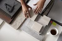 Overhead view of interior designer examining tiles at desk in office 11100034338| 写真素材・ストックフォト・画像・イラスト素材|アマナイメージズ
