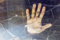 Close-up of hand on broken car window
