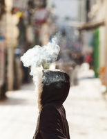 Digital composite image of smoke coming out from woman's hood