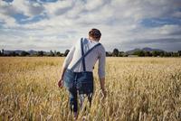 Rear view of female farmer walking on cultivated field 11100034378| 写真素材・ストックフォト・画像・イラスト素材|アマナイメージズ